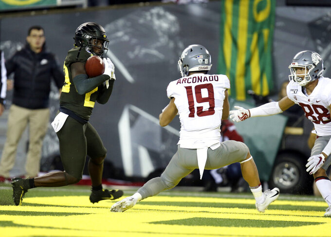 Oregon's Verone McKinley III, left, intercepts a tipped pass intended for Washington State's Brandon Arconado, center, as WSU's Rodrick Fisher moves in at right during the second quarter of an NCAA college football game Saturday, Oct. 26, 2019, in Eugene, Ore. (AP Photo/Chris Pietsch)
