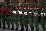 Soldiers hold a Mexican national flag as they prepare to raise it at half-staff during a ceremony marking the 34th anniversary of the 1985 earthquake, in Mexico City, Thursday, Sept. 19, 2019. The 8.1-magnitude earthquake killed as many as 10,000 and left thousands homeless. The date also commemorates the 2017 earthquake that rattled the city killing hundreds. (AP Photo/Marco Ugarte)