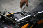 A biker drips in a few ounces of gasoline that he said he was able to catch from drops that dribbled from the pipe of a tanker as it supplied a gas station in Caracas, Venezuela, Sunday, May 31, 2020. After decades of being the cheapest gasoline in the world, Venezuelan President Nicolas Maduro indicates that as of next Monday a new pricing scheme will be imposed on some 200 stations. (AP Photo/Matias Delacroix)