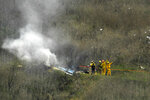 FILE - In this Jan. 26, 2020, file photo, firefighters work the scene of a helicopter crash where former NBA star Kobe Bryant died in Calabasas, Calif. Federal investigators said Wednesday, June 17, 2020, that the pilot of the helicopter that crashed in thick fog, killing Kobe Bryant and seven other passengers, reported he was climbing when he actually was descending.  (AP Photo/Mark J. Terrill, File)
