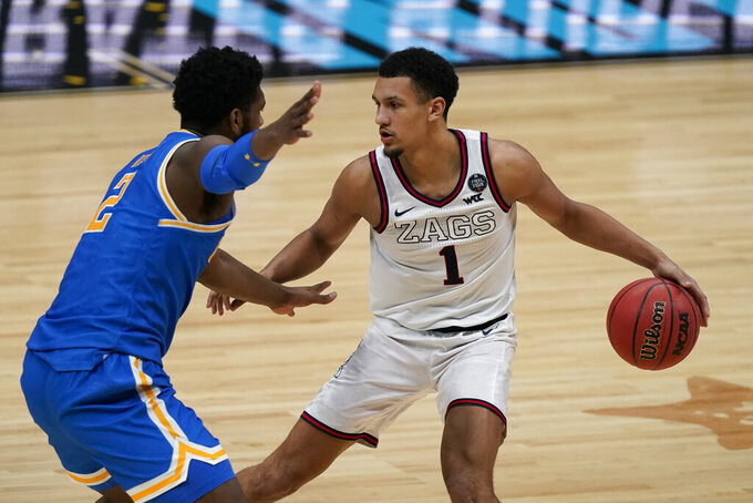 Gonzaga guard Jalen Suggs (1) looks to drive around UCLA forward Cody Riley (2) during the second half of a men's Final Four NCAA college basketball tournament semifinal game, Saturday, April 3, 2021, at Lucas Oil Stadium in Indianapolis. (AP Photo/Michael Conroy)