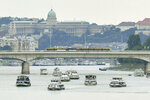 Backdropped by the Royal Castle on the top of Castle Hill a flotilla sails on River Danube during the funeral ceremony of the two Hungarian victims of the boat accident last May in Budapest, Hungary, Friday, July 12, 2019. They were the two crew members of a tourist boat carrying 33 South Korean tourists that was crashed by a large river cruise ship and sank in River Danube at a pier of Margaret Bridge in Budapest on May 29, killing 28 people. Seven Korean tourists survived the accident. (Zoltan Mathe/MTI via AP)