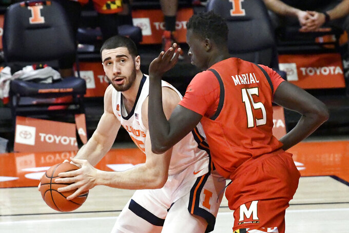 Illinois forward Giorgi Bezhanishvili (15) looks to pass as he is pressured by Maryland center Chol Marial (15) in the first half of an NCAA college basketball game, Sunday, Jan. 10, 2021, in Champaign, Ill. (AP Photo/Holly Hart)