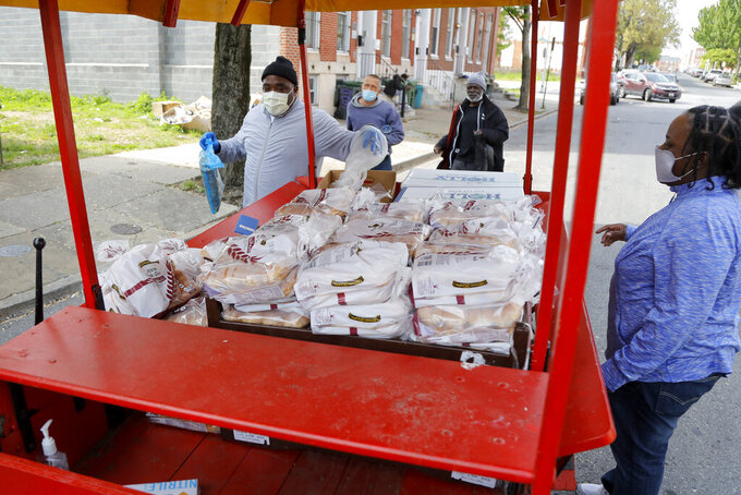An Arabber, left, hands out free chicken and bread for West Baltimore residents in a horse-drawn cart, Wednesday, April 29, 2020. The 2,000 pounds of frozen chicken, which was donated to the University of Maryland, Baltimore from Holly Poultry, was delivered to residents by the Arabbers, street vendors who sell fruits and vegetables from colorful horse-drawn carts. The university estimated the donation will reach about 900 families as they help battle food concerns during the new coronavirus outbreak. (AP Photo/Julio Cortez)