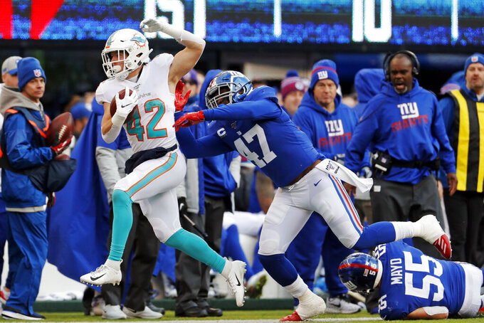 Miami Dolphins running back Patrick Laird (42) runs past New York Giants outside linebacker Alec Ogletree (47) and Giants outside linebacker David Mayo (55) in the second half of an NFL football game, Sunday, Dec. 15, 2019, in East Rutherford, N.J. (AP Photo/Adam Hunger)