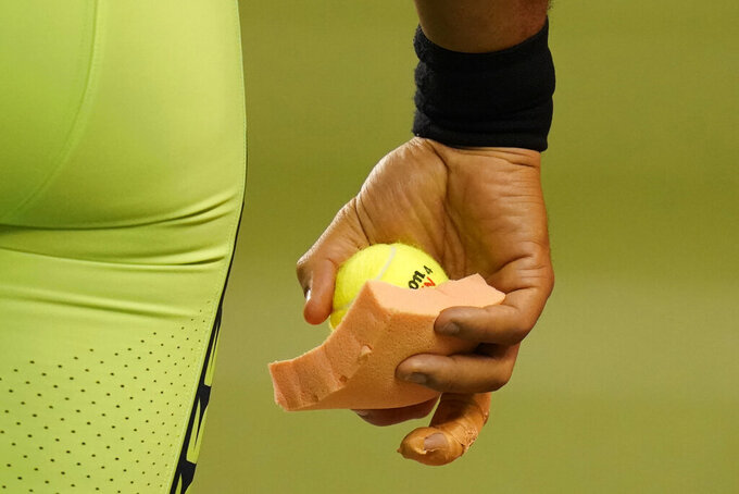 Seattle Seahawks quarterback Russell Wilson holds a sponge and a tennis ball near his taped injured finger during the fourth quarter of an NFL football game against the Los Angeles Rams, Thursday, Oct. 7, 2021, in Seattle. Wilson left the game after the injury and the Rams won 26-17. (AP Photo/Elaine Thompson)