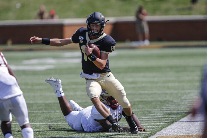 Wake Forest quarterback Michael Kern (15)avoids Elon defensive lineman Destin Flloyd as he carries the football in the second half of an NCAA college football game in Winston-Salem, N.C., Saturday, Sept. 21, 2019. Wake Forest won 49-7. (AP Photo/Nell Redmond)