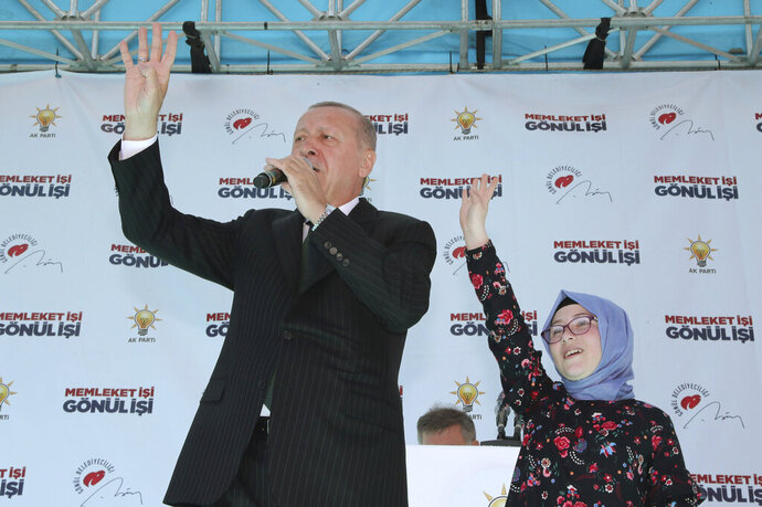 Turkey's President Recep Tayyip Erdogan waves to the supporters of his ruling Justice and Development Party with a young supporter, Sevval Cerrah, during a rally in Eregli, Turkey, Tuesday, March 19, 2019. Ignoring widespread criticism, Erdogan has again shown excerpts of a video taken by the attacker who killed 50 people in mosques in New Zealand at a campaign rally. (Presidential Press Service via AP, Pool)