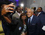 Mike Espy who is seeking to unseat appointed Sen. Cindy Hyde-Smith, R-Miss., and serve the last two years of the six-year term vacated when Republican Thad Cochran retired for health reasons, takes a photo with a supporter following his speech in Jackson, Miss., Tuesday night, Nov. 6, 2018. Espy will face Hyde-Smith in a runoff, Nov. 27. (AP Photo/Rogelio V. Solis)