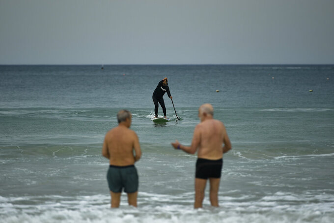 A surferin the sea, while two old men talks, at La Concha beach, after lockdown restrictions were lifted, in San Sebastian, northern Spain, Sunday, May 9, 2021. Impromptu street celebrations erupted across Spain as the clock struck midnight on Saturday, when a six-month-long national state of emergency to contain the spread of coronavirus ended and many nighttime curfews were lifted. (AP Photo/Alvaro Barrientos)