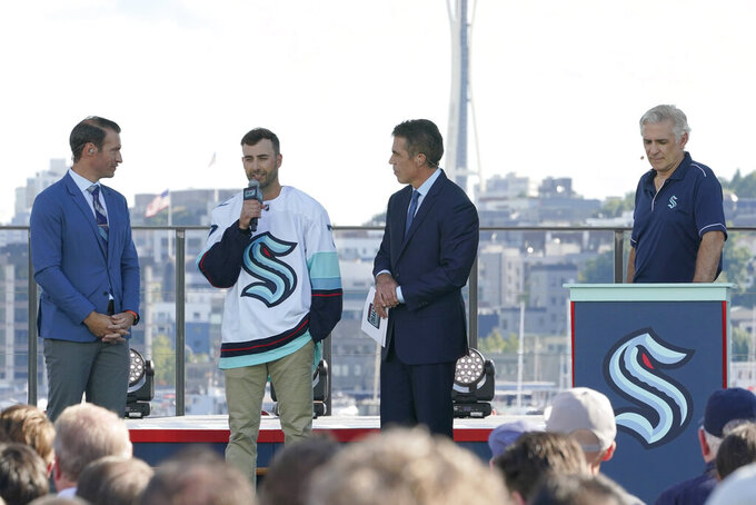 Jordan Eberle, second from left, a forward from the New York Islanders, is introduced as a new player for the Seattle Kraken as he stands with ESPN NHL hockey draft hosts Dominic Moore, left, and Chris Fowler, second from right, Wednesday, July 21, 2021, as Kraken general manager Ron Francis, right, listens during the Kraken's NHL hockey expansion draft event in Seattle. (AP Photo/Ted S. Warren)