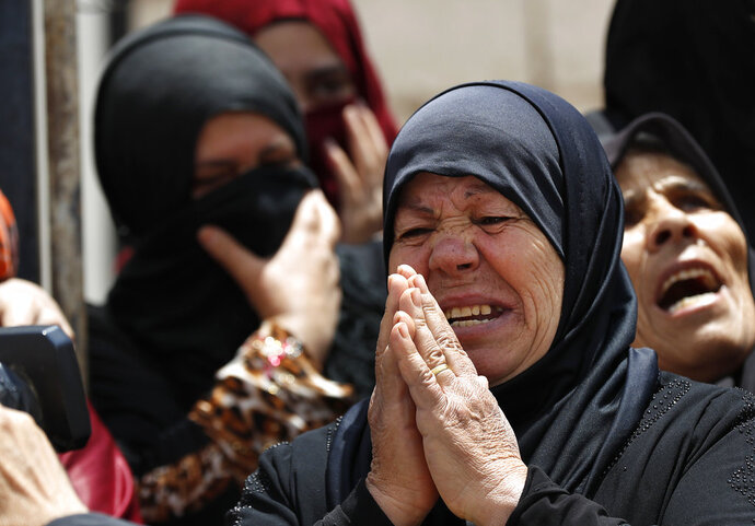 Syrian refugee women react during the visit of the Lebanese Foreign Minister Gibran Bassil to their informal refugee camp in Arsal, near the border with Syria, east Lebanon, Wednesday, June 13, 2018. A public spat between the Lebanese government and the United Nation's refugee agency deepened Wednesday as Lebanon's caretaker foreign minister kept up his criticism, accusing the agency of discouraging Syrian refugees from returning home. Lebanon is home to more than a million Syrian refugees, or about a quarter of the country's population, putting a huge strain on the economy. (AP Photo/Hussein Malla)