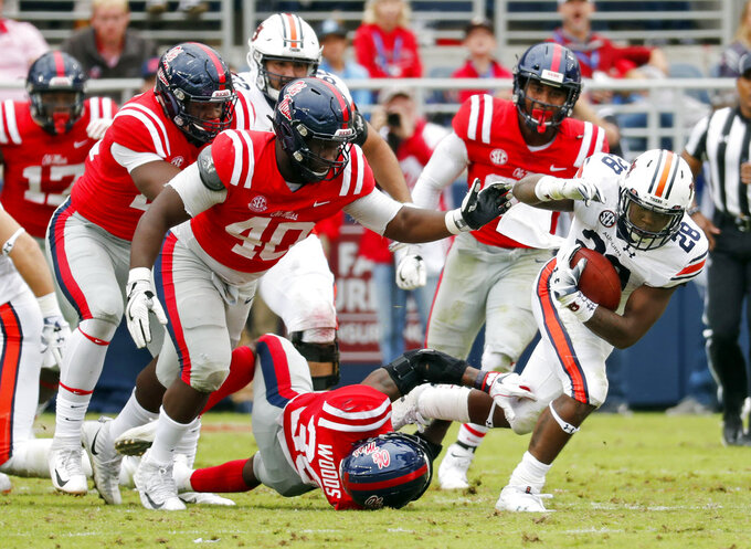 Auburn running back JaTarvious Whitlow (28) rushes for a first down as Mississippi defenders pursue during the first half of an NCAA college football game, Saturday, Oct. 20, 2018, in Oxford, Miss. (AP Photo/Rogelio V. Solis)
