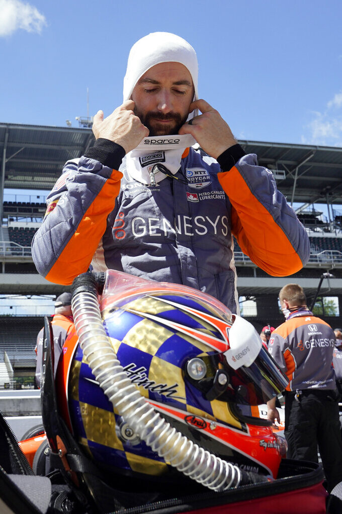 FILE- In this Aug. 16, 2020, file photo, James Hinchcliffe, of Canada, takes off his balaclava after qualifying for the Indianapolis 500 auto race at the Indianapolis Motor Speedway in Indianapolis. Hinchcliffe will return to Andretti Autosport for the final three races of the season to fill the seat left vacant when Zach Veach stepped out of the car earlier this week, Andretti Autosport announced Friday, Sept. 25, 2020. (AP Photo/Darron Cummings, File)