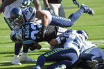 Carolina Panthers running back Christian McCaffrey (22) is tackled by Seattle Seahawks middle linebacker Bobby Wagner (54) and outside linebacker K.J. Wright (50) during the first half of an NFL football game in Charlotte, N.C., Sunday, Dec. 15, 2019. (AP Photo/Mike McCarn)