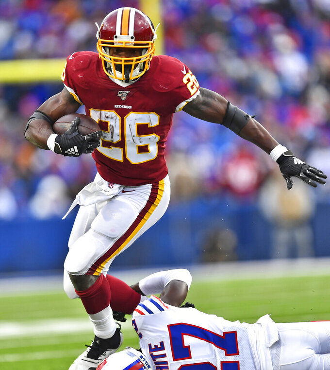 Washington Redskins running back Adrian Peterson (26) avoids a tackle by Buffalo Bills cornerback Tre'Davious White (27) during the second half of an NFL football game, Sunday, Nov. 3, 2019, in Orchard Park, N.Y. (AP Photo/Adrian Kraus)