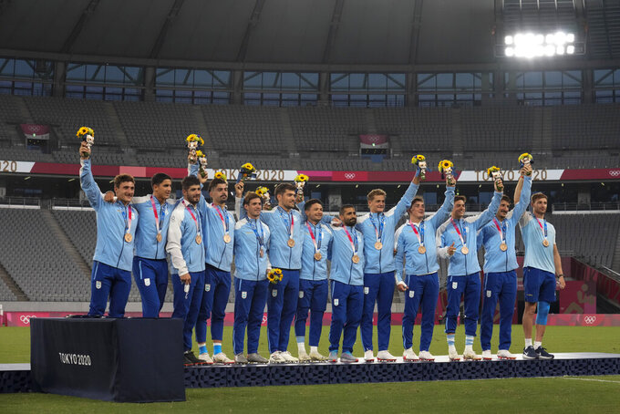 CORRECTS TO BRONZE FROM SILVER - Argentina players celebrate on the podium wearing their bronze medals in men's rugby sevens, at the 2020 Summer Olympics, Wednesday, July 28, 2021 in Tokyo, Japan. (AP Photo/Shuji Kajiyama)