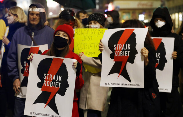Protesters hold signs reading in Polish