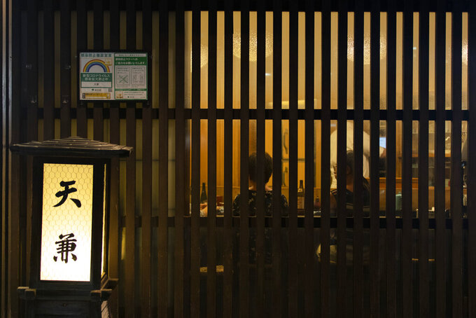 People have dinner at a restaurant in Tokyo on Friday, July 9, 2021. A state of emergency began Monday, July 12, 2021, in Tokyo, as the number of new cases is climbing fast and hospital beds are starting to fill just 11 days ahead of the Tokyo Olympics. (AP Photo/Hiro Komae)