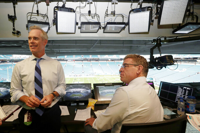 FILE - In this Aug. 23, 2019, file photo, Fox Sports play-by-play announcer Joe Buck, left, and analyst Troy Aikman, right, work in the broadcast booth before a preseason NFL football game between the Miami Dolphins and Jacksonville Jaguars in Miami Gardens, Fla. Chris Myers and Erin Andrews will be doing a little bit of everything on the sidelines for Fox's broadcast of Super Bowl 54. Not only will they be filing reports, but will be the eyes and ears for the production truck as well as Joe Buck and Troy Aikman in the booth. (AP Photo/Lynne Sladky, File)