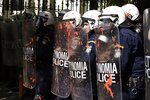 University students throw red paints at riot police during a protest outside the Ministry of Macedonia and Thrace in the northern Greek port city of Thessaloniki, Thursday, Oct. 24, 2019. Police clashed with students at demonstrations in Greece's two largest cities Thursday amid strikes and street protests against a planned overhaul of business and licensing rules by the new conservative government. (AP Photo/Giannis Papanikos)