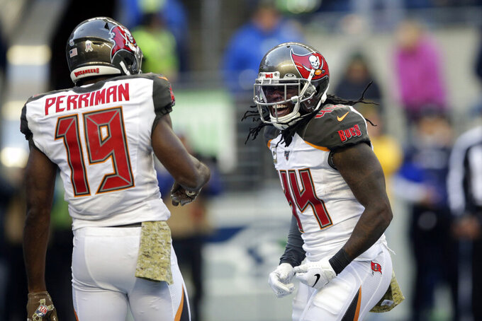 Tampa Bay Buccaneers running back Dare Ogunbowale, right, celebrates with wide receiver Breshad Perriman after rushing for a touchdown against the Seattle Seahawks during the second half of an NFL football game, Sunday, Nov. 3, 2019, in Seattle. (AP Photo/Scott Eklund)
