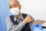 An elderly man receives his first dose of Pfizer's COVID-19 vaccine at Hachioji City Hall in Tokyo Monday, April 12, 2021. Japan started its vaccination drive with medical workers and expanded Monday to older residents, with the first shots being given in about 120 selected places around the country. (Kyodo News via AP)