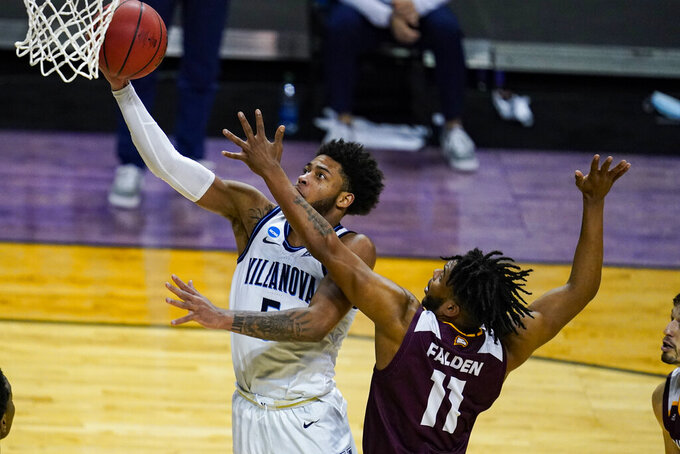 Villanova guard Justin Moore (5) shoots over Winthrop guard Charles Falden (11) in the second half of a first round game in the NCAA men's college basketball tournament at Farmers Coliseum in Indianapolis, Saturday, March 20, 2021. (AP Photo/Michael Conroy)