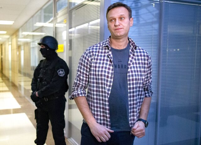 FILE- In this file photo taken on Thursday, Dec. 26, 2019, Russian opposition leader Alexei Navalny speaks to the media in front of security officers standing guard at the Foundation for Fighting Corruption office in Moscow, Russia. Police raids the offices of Alexei Navalny's Foundation for Fighting Corruption in Moscow, Russia, Friday, July 17, 2020. Opposition leader Navalny sees the move as politically motivated.(AP Photo/Alexander Zemlianichenko, File)