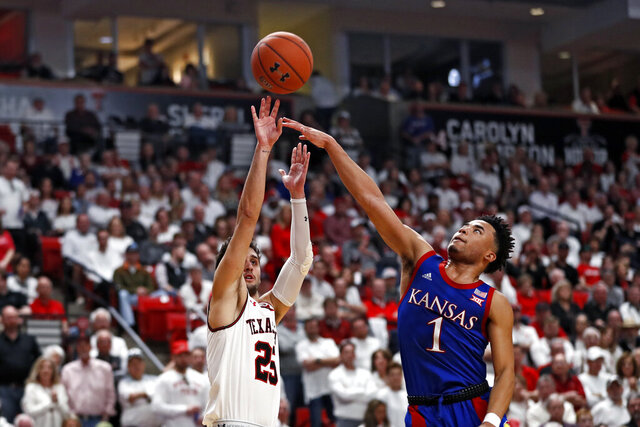 Texas Tech's Davide Moretti (25) shoots the ball over Kansas' Devon Dotson (1) during the first half of an NCAA college basketball game Saturday, March 7, 2020, in Lubbock, Texas. (AP Photo/Brad Tollefson)