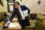 Rep. Nick Bain, R-Corinth, packs up his desk as he moves to another desk in the Mississippi House chambers, Tuesday, Jan. 7, 2020, in Jackson, Miss. Lawmakers spent much of the afternoon getting parking and seating assignments arranged. (AP Photo/Rogelio V. Solis)