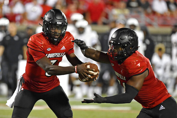 Louisville quarterback Malik Cunningham (3) hands the ball off to running back Maurice Burkley (36) during the second half of an NCAA college football game against Central Florida in Louisville, Ky., Friday, Sept. 17, 2021. (AP Photo/Timothy D. Easley)