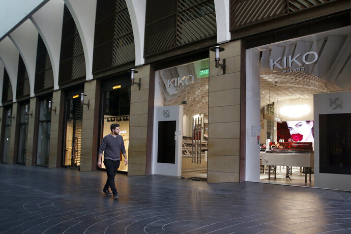 In this Monday, March 16, 2020 photo, a man walks past closed shops after authorities ordered the closure as part of the preventive measures against the preventive measures against the coronavirus, inside the upscale Beirut Souks shopping mall in Beirut, Lebanon. COVID-19 has managed to do what various wars could not: Close bars, restaurants and entertainment spots across the tiny Mediterranean country. The pandemic is an economic gut punch, delivered at a time when Lebanon is mired in the worst financial crisis in its history -- one that could hasten the country's long-feared economic collapse. (AP Photo/Bilal Hussein)