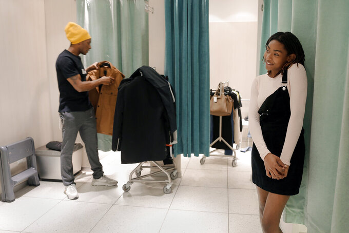 Houston Texans player De'Andre Hopkins, left, goes through outfits on a rack as Miracle Washington-Tribble checks her look in the mirror in a fitting area at H&M during a shopping spree Monday, Dec. 16, 2019, at Galleria Mall in Houston. Washington-Tribble and Jadon Cofield are beneficiaries of Eight Million Stories, a Houston program which helps 14-18-year-olds who have either quit or been kicked out of school continue their education, find employment and receive emotional support. (AP Photo/Michael Wyke)