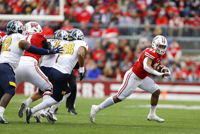 Wisconsin running back Jonathan Taylor runs away from Kent State defensive lineman Theo Majette (92) and linebacker Nick Faulkner (1) and linebacker Mandela Lawrence-Burke (28) during the first half of an NCAA college football game Saturday, Oct. 5, 2019, in Madison, Wis. Wisconsin won 48-0. (AP Photo/Andy Manis)