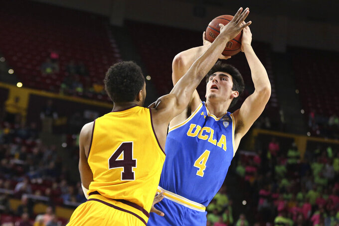 UCLA's Jamie Jaquez Jr., right, puts up a shot against Arizona State's Kimani Lawrence during the first half of an NCAA college basketball game Thursday, Feb. 6, 2020, in Tempe, Ariz. (AP Photo/Darryl Webb)