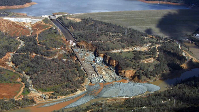 FILE - This Feb. 27, 2017, file image provided by KCRA shows Oroville Dam's crippled spillway in Oroville, Calif. California's water resources agency has agreed to pay a Northern California county $12 million for repair roads after a crisis at the country's tallest dam forced nearly 200,000 people to evacuate in 2017. The state Department of Water Resources and Butte County announced the settlement Tuesday, Oct. 15, 2019, more than two years after spillways at the Oroville Dam crumbled and fell away during heavy rains. (KCRA via AP, File)