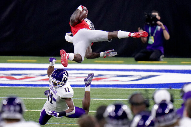 Ohio State running back Trey Sermon, top, is sent flying by Northwestern defensive back A.J. Hampton (11) during the first half of the Big Ten championship NCAA college football game, Saturday, Dec. 19, 2020, in Indianapolis. (AP Photo/AJ Mast)