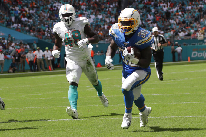 Los Angeles Chargers running back Troymaine Pope (35) runs for a touchdown ahead of Miami Dolphins linebacker Sam Eguavoen (49), during the first half at an NFL football game, Sunday, Sept. 29, 2019, in Miami Gardens, Fla. AP Photo/Lynne Sladky)