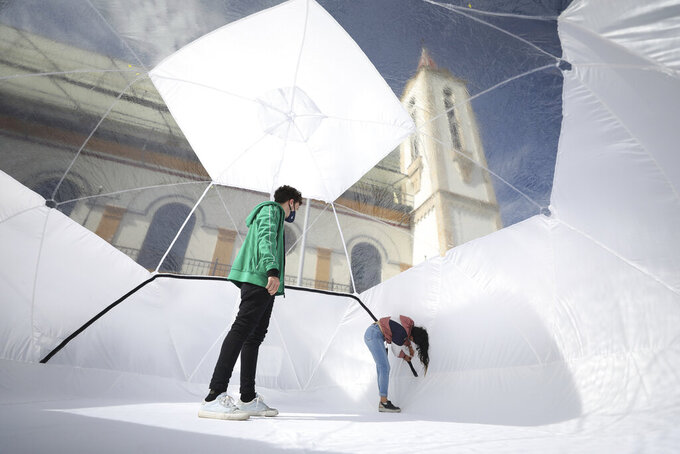 Designers stand inside a Portable Epidemiological Insulation Unit during a media presentation, in Bogota, Colombia, Tuesday, Feb. 16, 2021. Colombia's La Salle University school of architecture designed the small polyhedral pneumatic geodesic domes which can be used to isolate and treat COVID-19 patients in areas where there are no nearby hospitals or where existing hospitals are overwhelmed with patients. (AP Photo/Fernando Vergara)