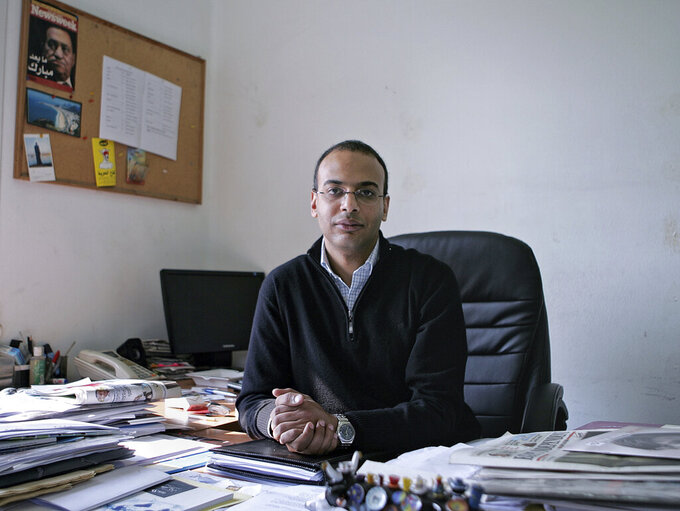 FILE -- In this Dec. 7, 2011 file photo, Hossam Bahgat sits for a photograph, in his office at the Egyptian Initiative for Personal Rights in Cairo, Egypt. On Sunday, July 18, 2021, Egypt released two activists and a journalist after they spent months in pre-trial detention. The releases came amid an outcry by rights advocates after prosecutors last week referred Hossam Bahgat, a leading Egyptian investigative journalist and human rights advocate, to trial over accusations of insulting the election authority, spreading false news alleging electoral fraud; and using social media to commit crimes, Bahgat said. (Sarah Rafea via AP, File)