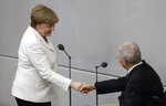 German Chancellor Angela Merkel is congratulated by Parliament President Wolfgang Schaeuble after Merkel was sworn-in for a fourth term as chancellor in the German parliament Bundestag in Berlin, Germany, Wednesday, March 14, 2018. (AP Photo/Michael Sohn)
