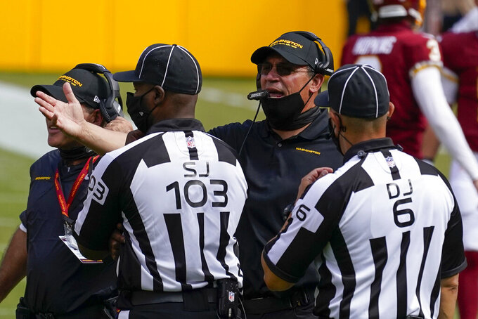 Washington Football Team head coach Ron Rivera argues a call with side judge Eugene Hall (103) and down judge Jerod Phillips (6), during second half of an NFL football game against the Philadelphia Eagles, Sunday, Sept. 13, 2020, in Landover, Md. (AP Photo/Alex Brandon)