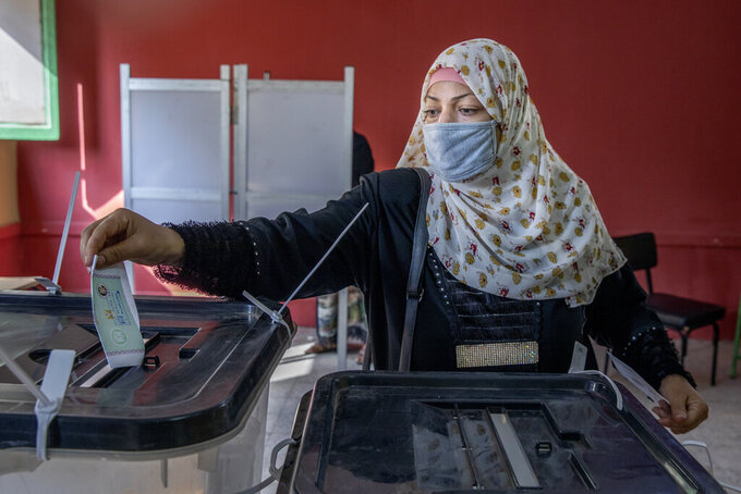 A woman casts her ballot on the first day of the parliamentary election inside a polling station in Giza, Egypt, Saturday, Oct. 24, 2020. Egyptians began voting Saturday in the first stage of a parliamentary election, a vote that is highly likely to produce a toothless House of Representatives packed with supporters of President Abdel-Fattah el-Sissi. (AP Photo/Nariman El-Mofty)