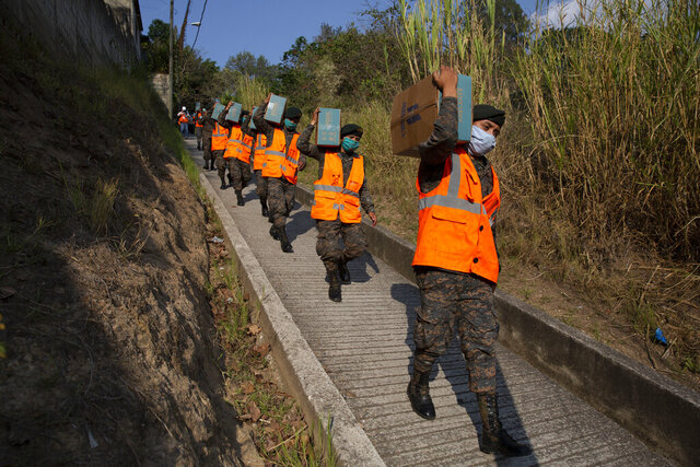 Soldiers carry boxes with food to deliver to the poor at the Santa Rosita neighborhood on the outskirts of Guatemala City, Monday, April 6, 2020, during a stay-at-home curfew designed to slow the spread of the new coronavirus. (AP Photo/Moises Castillo)