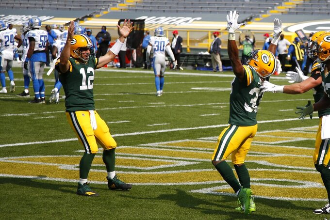 Green Bay Packers' Aaron Jones celebrates his touchdown run with Aaron Rodgers (12) during the second half of an NFL football game against the Detroit Lions Sunday, Sept. 20, 2020, in Green Bay, Wis. (AP Photo/Matt Ludtke)
