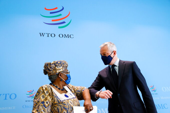 French Finance Minister Bruno Le Maire, right, and World Trade Organisation (WTO) Director-General Ngozi Okonjo-Iweala, left, elbow-bump after a joint news conference at WTO headquarters in Geneva, Switzerland, Thursday, April 1, 2021.(Denis Balibouse/Pool via AP)