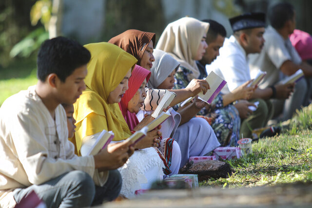 People read the holy book of the Quran as they pray at a mass grave site for the victims of the Indian Ocean tsunami, during the commemoration of the 15th anniversary of the disaster in Banda Aceh, Indonesia, Thursday, Dec. 26, 2019. (AP Photo/Nurhasanah)