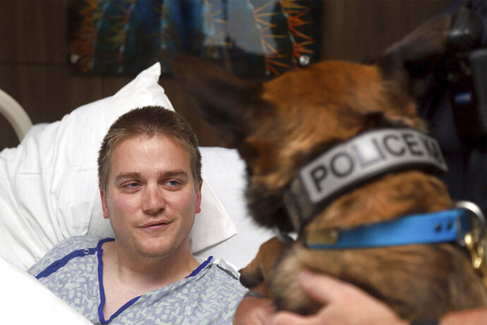 This photo provided by Piedmont Columbus Regional shows wounded Alabama police officer Webb Sistrunk getting a visit from his canine partner Leon at the hospital in Columbus, Ga., on Wednesday, May 22, 2019. Sistrunk was among several Auburn police officers shot while answering a call. One officer was killed, but Sistrunk is recovering. (Joseph T. Paull/Piedmont Columbus Regional via AP)