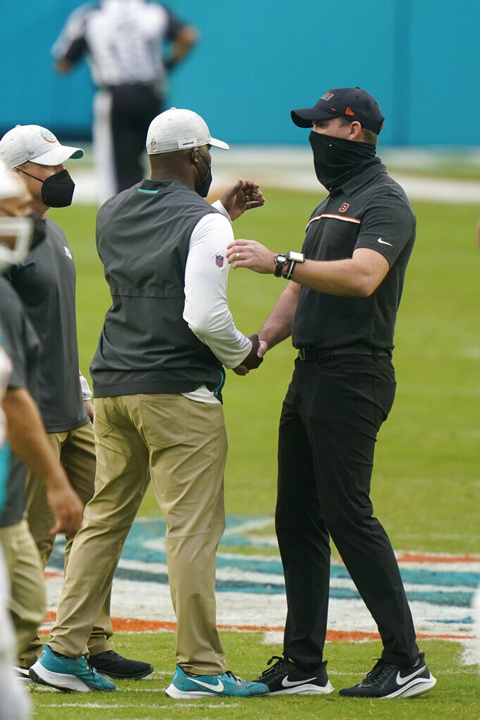 Miami Dolphins head coach Brian Flores greets Cincinnati Bengals head coach Zac Taylor at the end of an NFL football game, Sunday, Dec. 6, 2020, in Miami Gardens, Fla. The Dolphins defeated the Bengals 19-7. (AP Photo/Wilfredo Lee)
